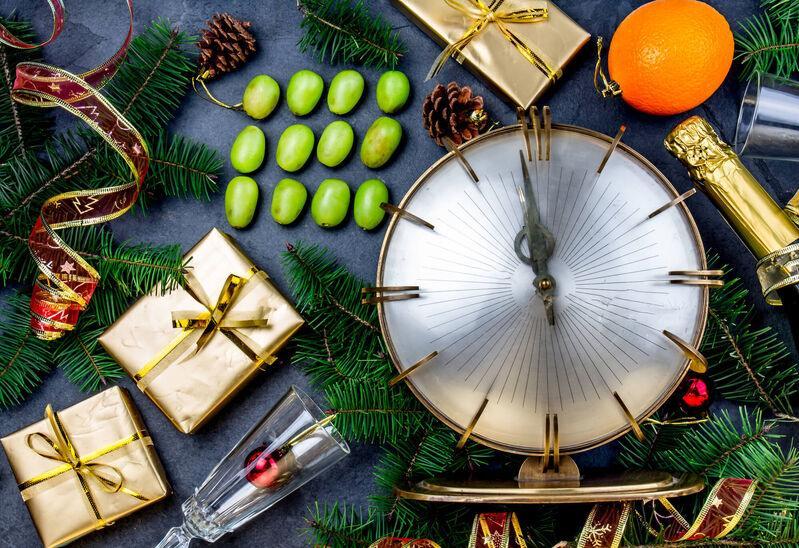 12 bobúľ hrozna vedľa hodín odpočítavajúcich Nový rok