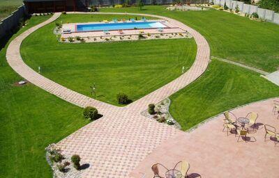 Trávnik okolo bazénu v penzióne Prima