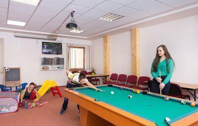 Staršie deti hrajúce biliard
