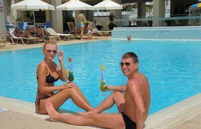 Párik s drinkom pri bazéne
