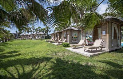 Malé domčeky s ležadlami na trávniku hotela Crystal Flora Beach Resort