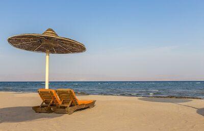 Ležadlá so slnečníkom na pláži pred hotelom The Bayview Taba Heights Resort
