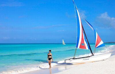Žena s plachetnicou na pláži