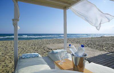 Pláž s ležadlami pred hotelom Anemos Luxury Grand Resort