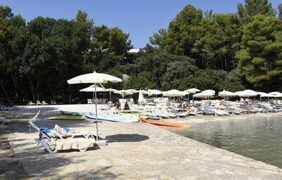 Pláž s ležadlami pred hotelom Capovaticano Resort Thalasso & Spa