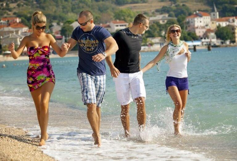 Dvojice idú popri mori po pláži