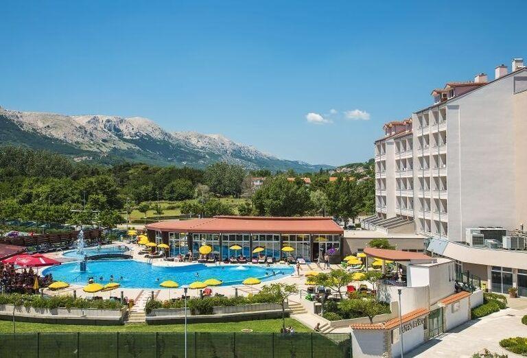 Pohľad na hotel Corinthia s bazénom v pozadí s horami