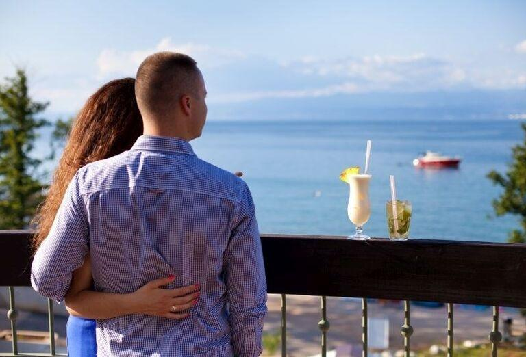 Párik popíjajúci miešané drinky a pozerajúci na more