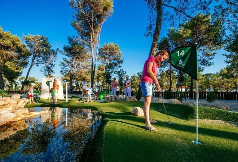 Dievča na golfe usilujúce sa trafiť jamku