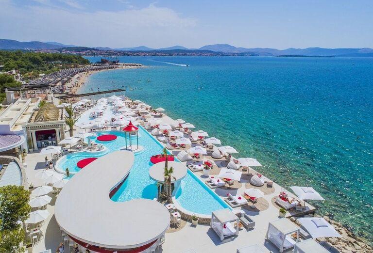 Pohľad na bazén s lehátkami a výhľadom na more hotela Amadria Park Ivan