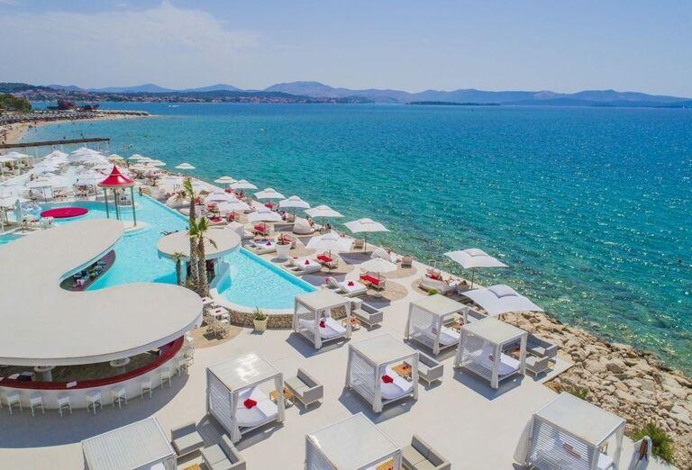 Bazén s lehátkami a výhľadom na more hotela Amadria Park Adrija