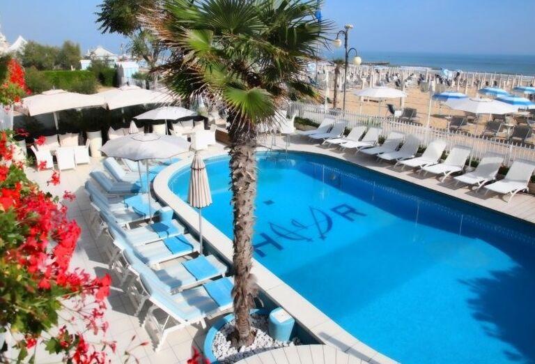 Bazén s ležadlami a slnečníkmi v hoteli Rivamare