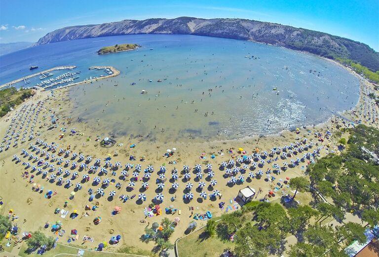 Piesková pláž so slnečníkmi pri hoteli Veli Mel