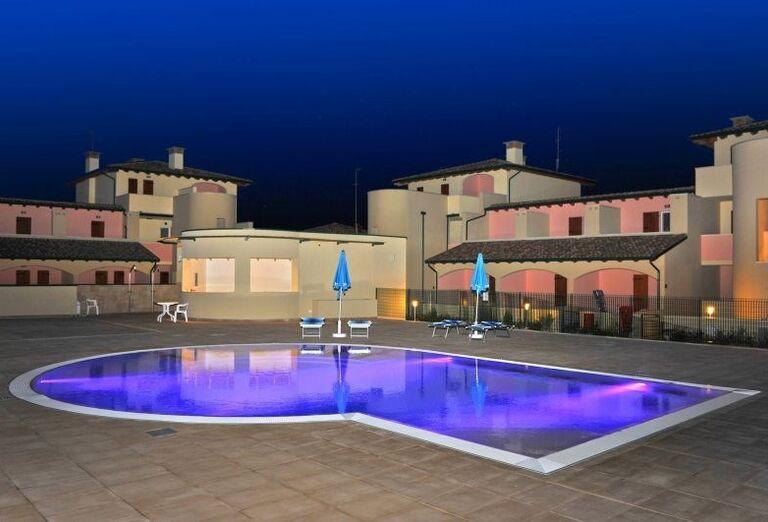 Večerný pohľad na bazén v rezidencii Airone Bianco
