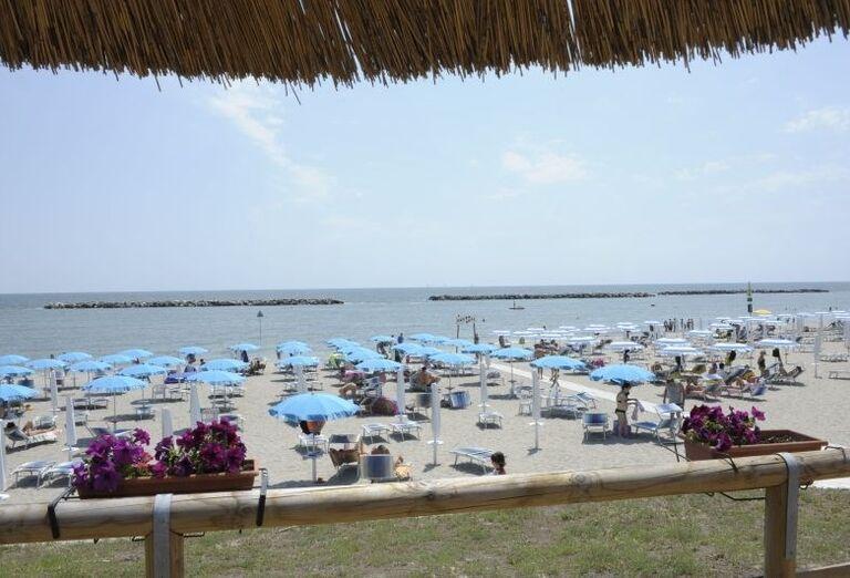 Pláž s ležadlami a slnečníkmi pred rezidenciou Airone Bianco