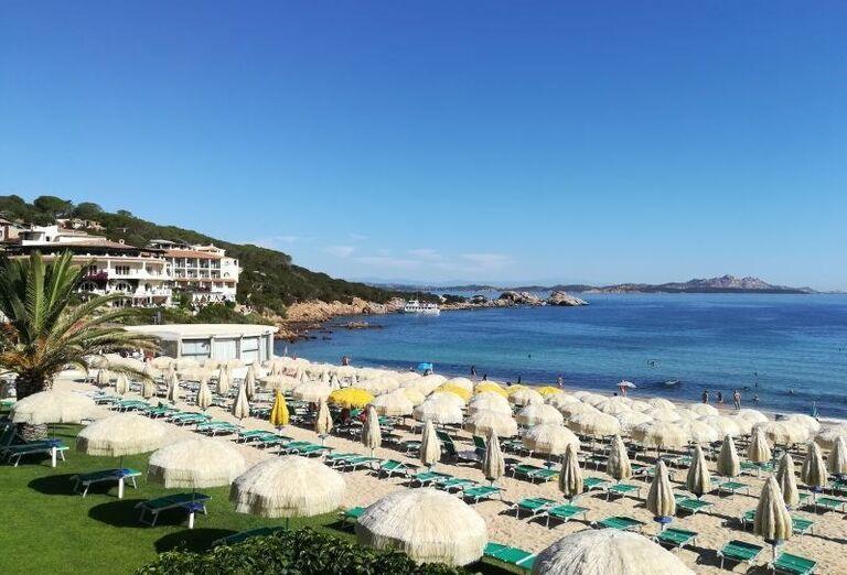 Piesková pláž s ležadlami a slnečníkmi pred hotelom Club Hotel Baja Sardinia