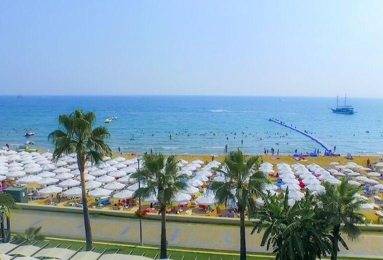 Pláž so slnečníkmi a ležadlami v hoteli Sandy Beach