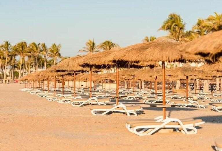 Ležadlá a slnečníky na pláži pri hoteli Fanar hotel and residences