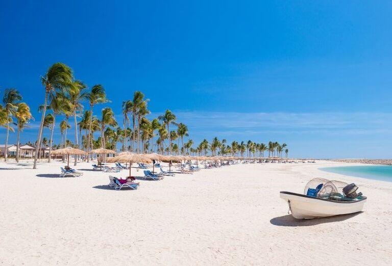 Čln na pláži s ležadlami a slnečníkmi