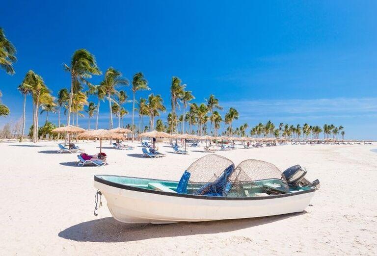 Čln na pláži pri hoteli Fanar hotel and residences