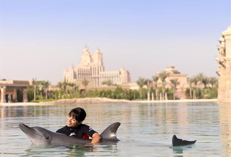 Žena plávajúca s delfínom