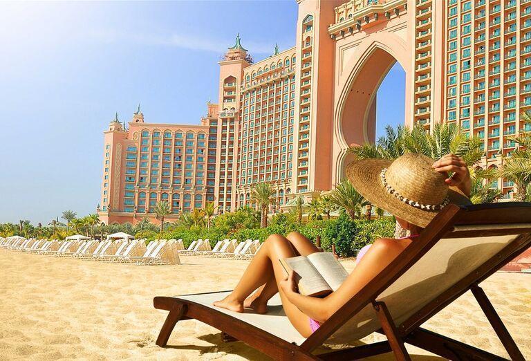 Žena oddychujúca na lehátku pred hotelom Atlantis, The Palm
