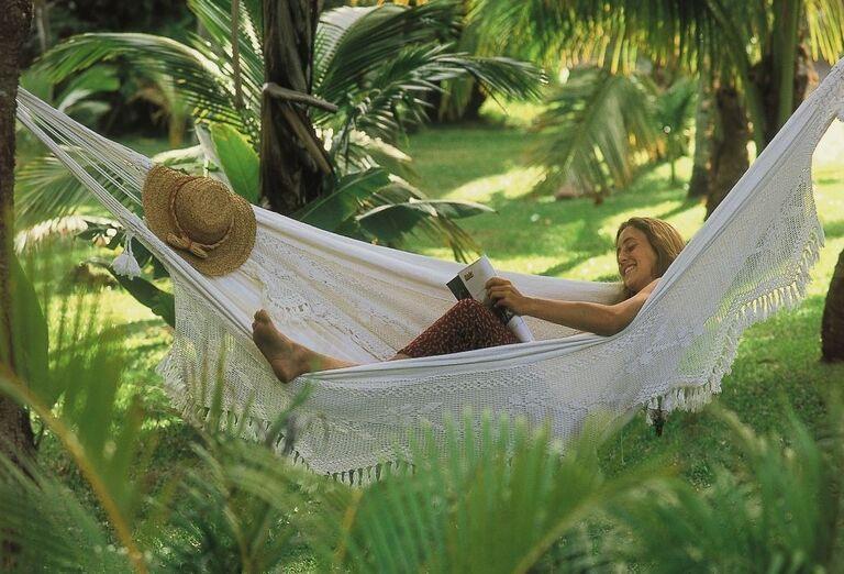 Žena čítajúca časopis v hojdacej siete