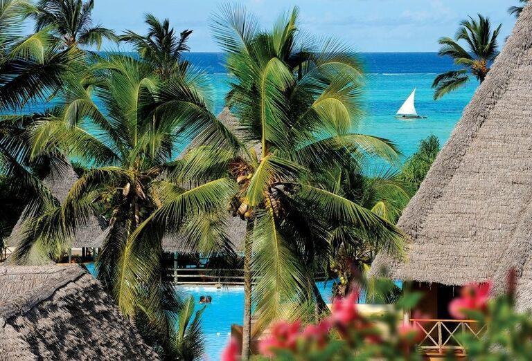 Bazén s palmami a morom v pozadí v hoteli Neptune Pwani Beach Resort & Spa