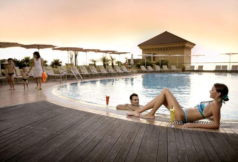 Párik oddychujúci v bazéne s drinkom