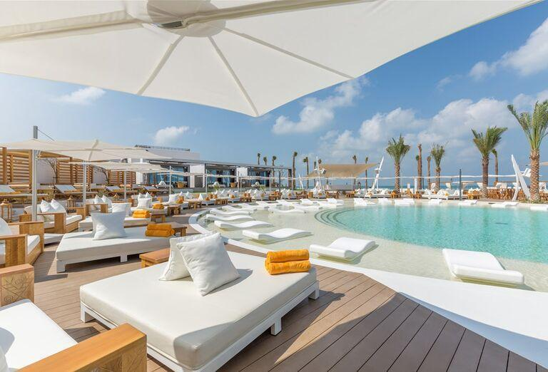 Bazén a pláž v pozadí hotela Nikki Beach Resort and Spa Dubai