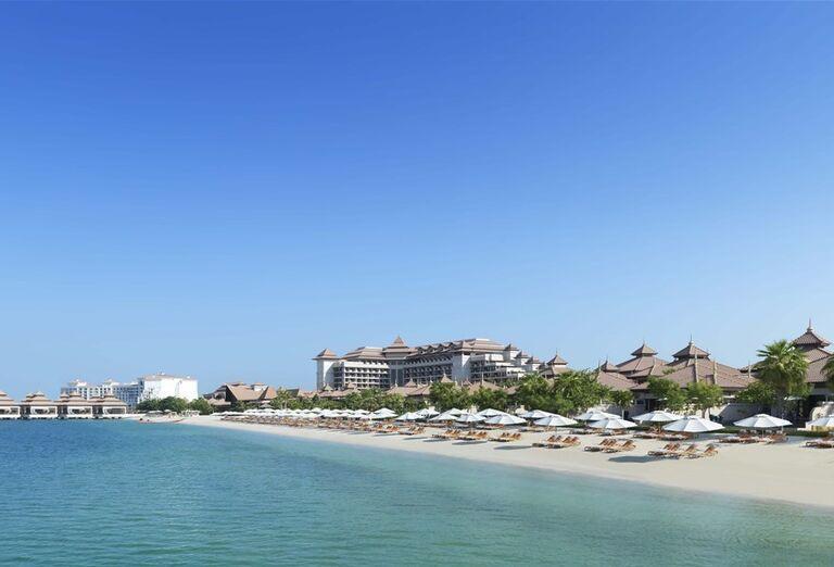Piesočnatá pláž s ležadlami a slnečníkmi v hoteli Anantara The Palm Dubai Resort