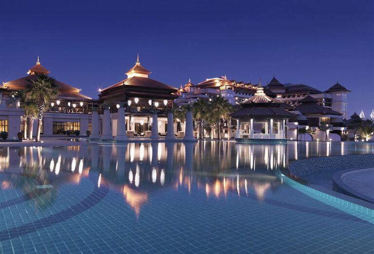 Pohľad od bazéna na večerný hotel Anantara The Palm Dubai Resort