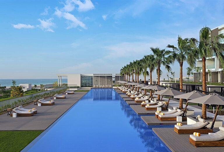 Ležadlá a slnečníky pri bazéne v hoteli The Oberoi Beach Resort Al Zorah