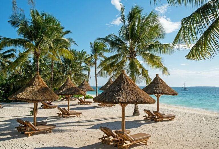 Ležadlá so slnečníkmi na pláži pred hotelom Zuri Zanzibar Hotel & Resort