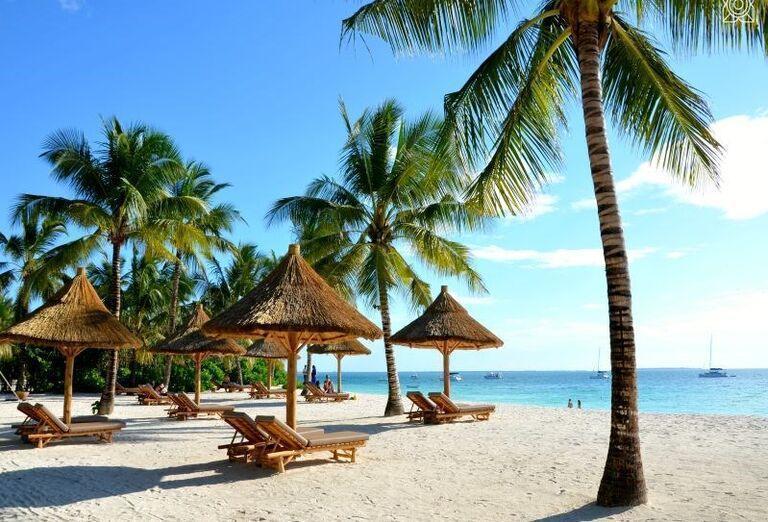 Pláž so slnečníkmi a ležadlami pred hotelom Zuri Zanzibar Hotel & Resort