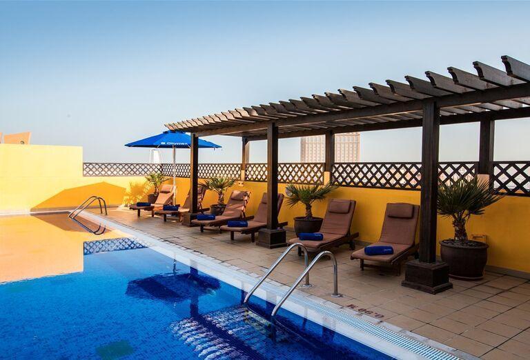 Ležadlá pri bazéne v hoteli City Max Al Barsha at the Mall
