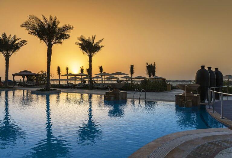 Bazén so západom slnka Hotel Ajman Saray