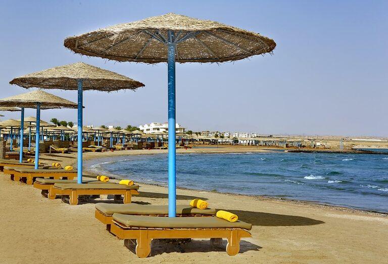 Pláž s ležadlami a slnečníkmi pred hotelom Hilton Hurghada Long Beach Resort