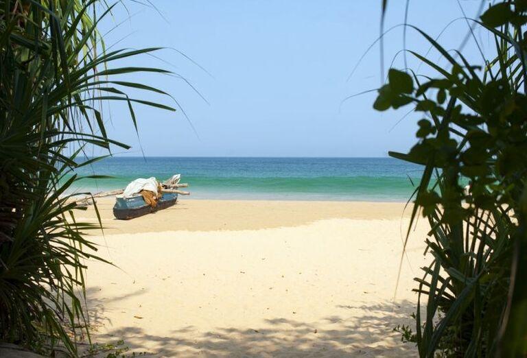Loďka na pieskovej pláži pri rezorte Surya Lanka Ayurveda Beach