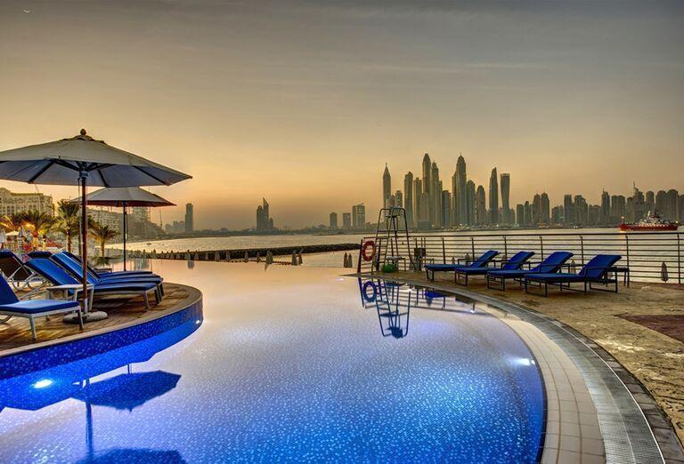 Ležadlá pri bazéne s výhľadom na mesto v hoteli Dukes Dubai
