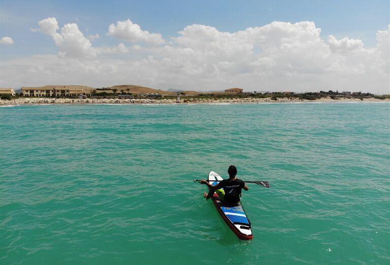 Muž sediaci na surfe na mori
