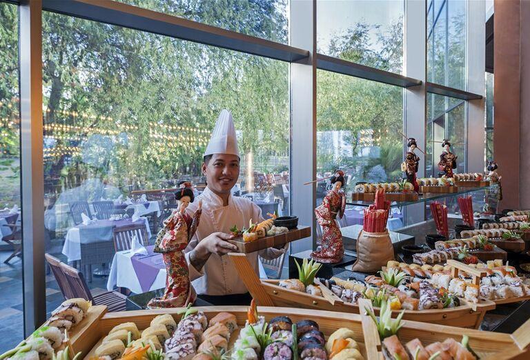 Čašník pri ponuke švédskych stolov v hoteli Noah´s Ark Deluxe Hotel