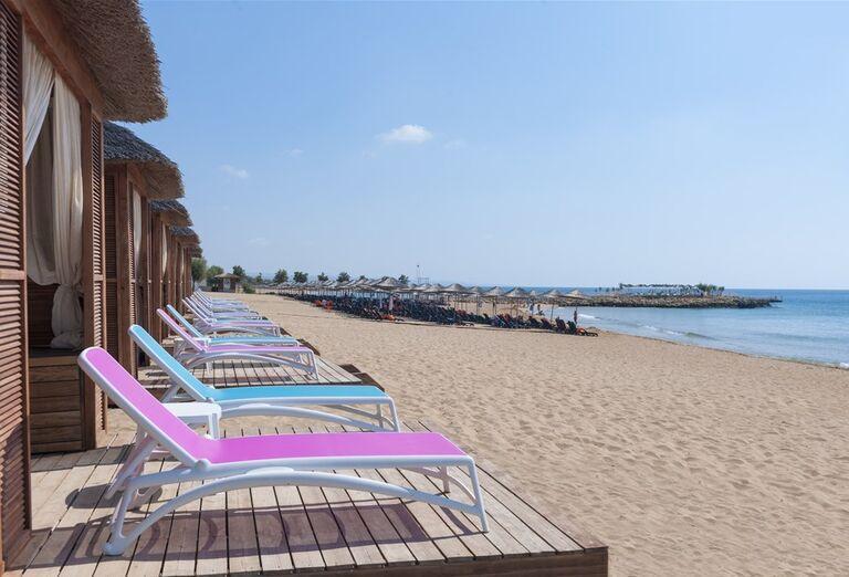 Ležadlá na pláži pred hotelom Noah´s Ark Deluxe Hotel