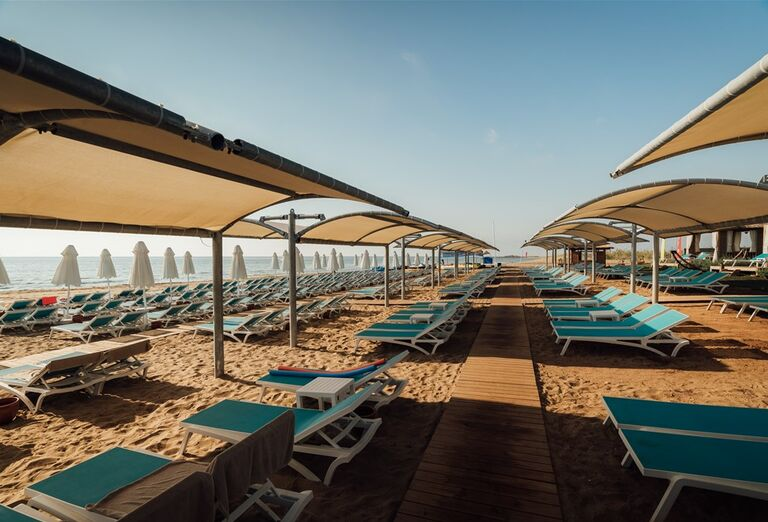 Krásna piesková pláž so slnečníkmi pred hotelom Limak Cyprus
