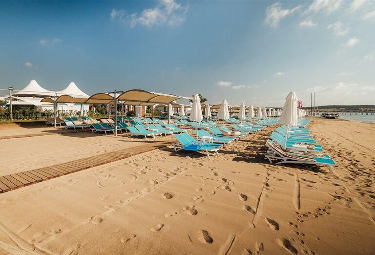 Piesková pláž s ležadlami v hoteli Limak Cyprus