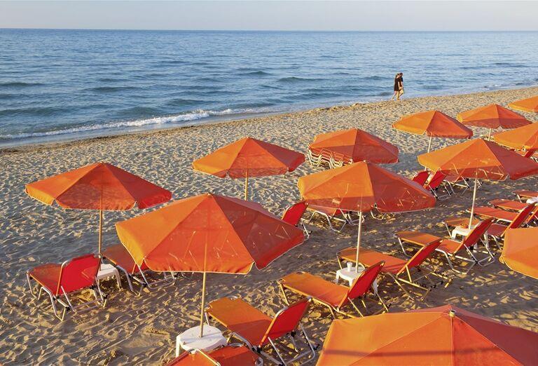 Piesková pláž s ležadlami a slnečníkmi pred hotelom Eden Village Kournas
