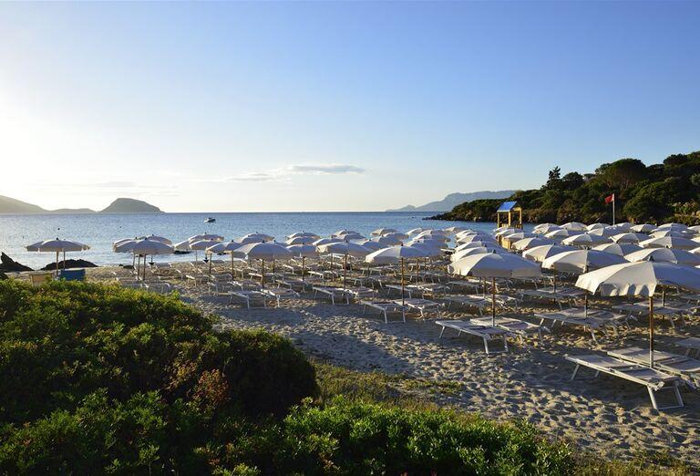 Pláž so slnečníkmi a ležadlami pred hotelom VOI Colonna Beach