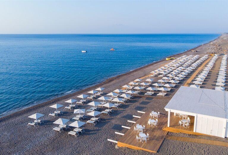 Pláž so slnečníkmi a ležadlami pred hotelom Gennadi Grand Resort