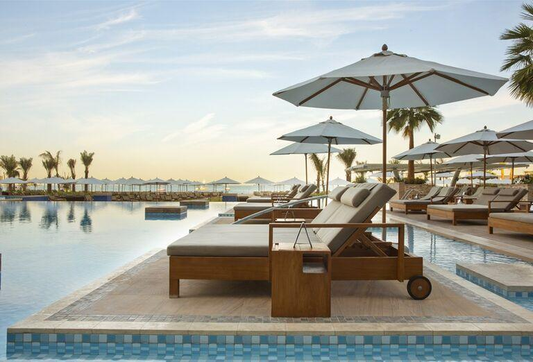 Ležadlá so slnečníkom pri bazéne v hoteli Rixos Premium Dubai