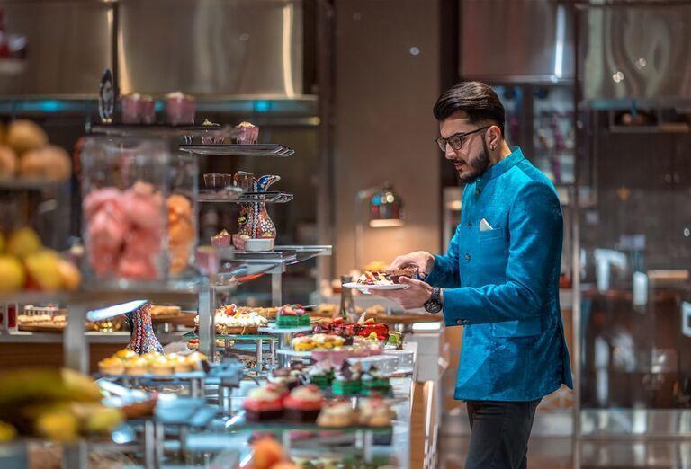 Muž pri výbere zo švédskych stolov